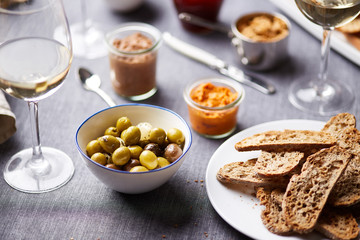 Green olives and crunchy slices bread on table.