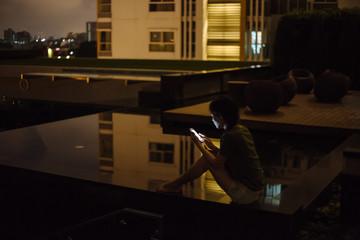 Woman using phone at pool beside building