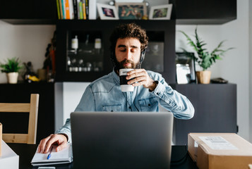 Man at desk with laptop taking break with cup of coffee.