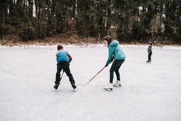 kids playing hockey on frozen pond
