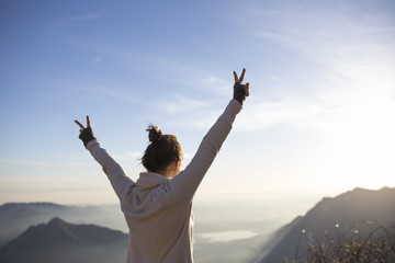 Young woman making the V sign on the top of the mountain