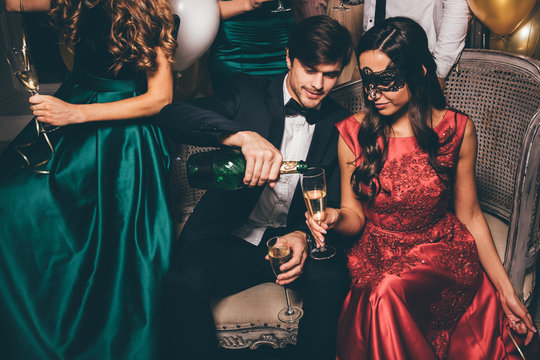 Man pouring women glasses with sham