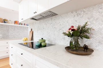 Rear kitchen bench styled with cut flowers and colorful saucepans