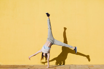 Young woman doing handstand in front of a yellow wall.