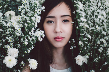 Beautiful young east asian woman portrait from the flower bush