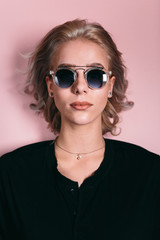 Blonde woman wearing sunglasses with pink background