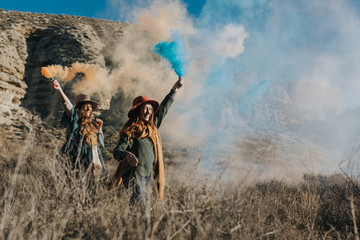 Cheerful teenagers playing with color smoke bombs in the countryside
