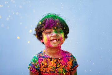 Portrait of cute little girl being showered by colored powders during holi