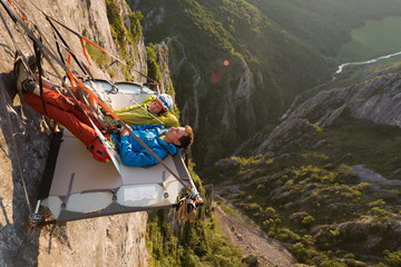 Rock climbing couple laying down on their portaledge