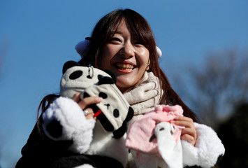 Panda enthusiast Saeko Nishitani poses for photograph after public viewing of female baby panda Xiang Xiang, born from mother panda Shin Shin on June 12, on first day of public debut at Ueno Zoological Gardens in Tokyo