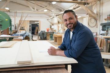 Side portrait of smiling hispanic cabinet shop worker