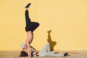Couple kissing whilst doing acrobatics in front of a yellow wall.