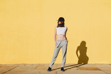 Fit woman wearing sport clothes standing in front of a yellow wall.