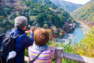 Tourist taking pictures of the river and forest in autumn season at Arashiyama