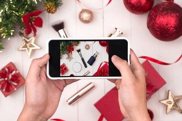 Hands holding mobile taking photo of christmas make up cosmetics products