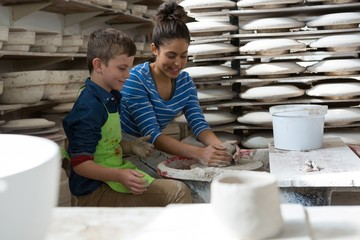 Female potter assisting a boy