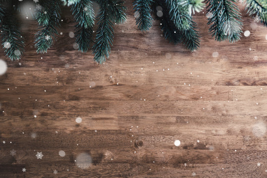 Green Christmas tree pine leaves and snow on wood table background