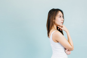 Attractive Asian woman thinking and arms crossed isolated on blue pastel background