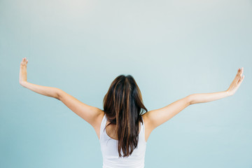 Back of beautiful young woman with arms raised over blue green background
