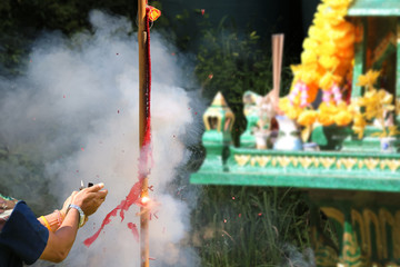 Asian people with firecrackers pay respect to shrine or spirit worship