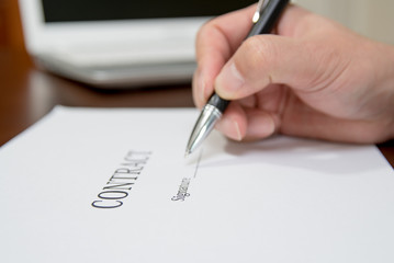 A concept of signing a contract holding a pen.  Defocused