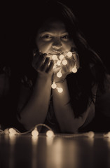 Vintage woman portrait with string lights - Sepia toned portrait of a young attractive woman with long hair sitting on the floor, in a dark room, holding in her hands a string of lights.