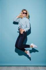 Full length image of Joyful woman in shirt and sunglasses