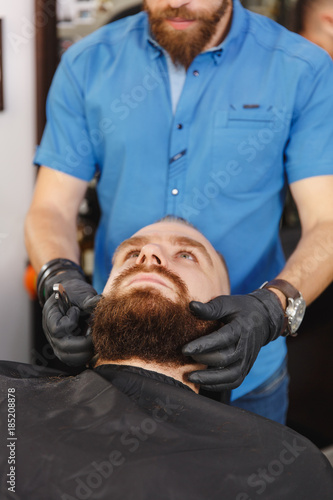 Male Professional Hairdresser Serving Client, Shaving Thick Big Beard  Straight Razor. Ginger Handsome Stylish