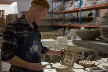 Male potter examining a clay