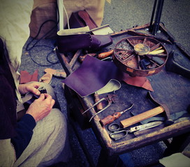 workshop with shoemaker during the processing of leather to produce shoes with antique effect