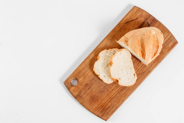 Top view of slices of white bread on a kitchen board, on a white background.