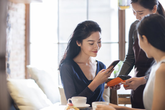 Friends paying with smart phone in cafe_