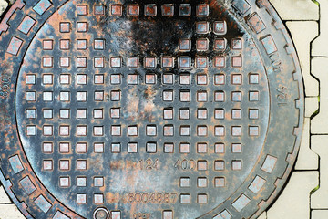 Metal drain cover on the pavement