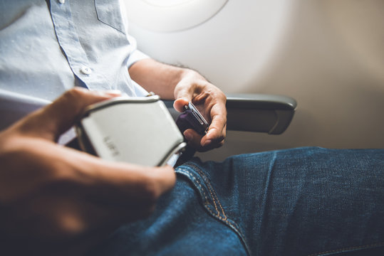 Passenger fastening seat belt while sitting on the airplane for safe flight