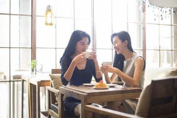 Best female friends drinking coffee in cafe_