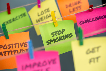 Sticky note with message stop smoking hanging on rope