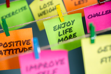 Sticky notes hanging with important message to enjoy life more