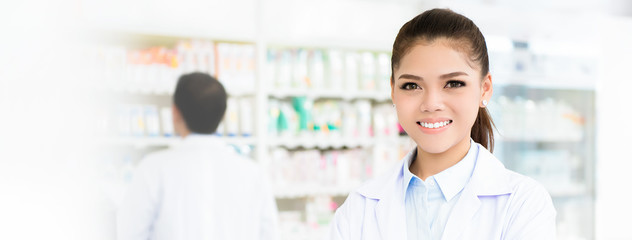 Photo sur Toile Pharmacie Smiling Asian female pharmacist in chemist shop or pharmacy