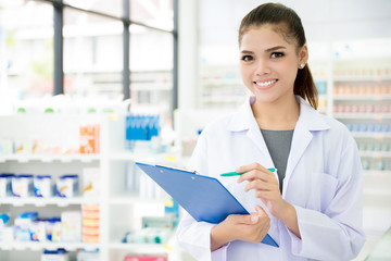 Photo sur Toile Pharmacie Asian female pharmacist working in chemist shop or pharmacy