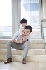 Cheerful father and son playing in the living room