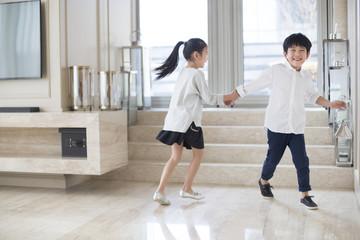 Happy siblings running in the living room