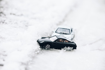 Symbolic car accident in winter on snow road staged with toy cars