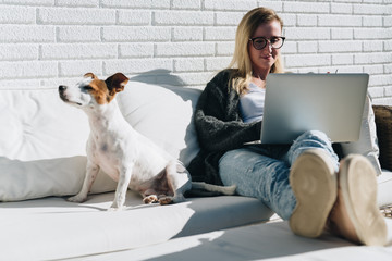 Sunny day. Young businesswoman is sitting on couch on terrace, using laptop. Dog sits on couch next to girl. Distance work, learning. Online marketing, education. Girl freelancer works at home.