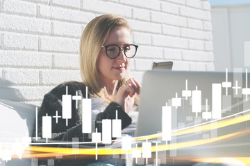 Young business woman in glasses sits at laptop and uses smartphone. In foreground charts of binary options. Girl working, learning online. Online marketing, education, e-learning.Business planning.