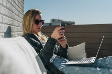 Sunny day. Young businesswoman is sitting on white couch on terrace, using laptop and smartphone. Hipster girl working, blogging, learning online. Distance work.Online marketing,education, e-learning.