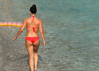 A girl in a red bikini with the turquoise waters of the Adriatic Sea