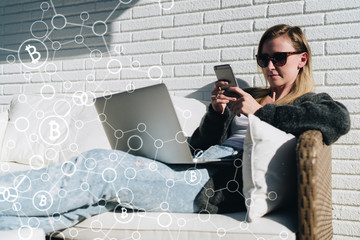 Young business woman in sunglasses sits and uses smartphone, laptop. In foreground infographics,bitcoin icons. Girl working, learning online. Online marketing, education, e-learning.Business planning.