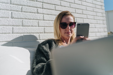 Sunny day.Young businesswoman is sitting on white couch on terrace,using laptop and smartphone.Hipster girl working,blogging,learning online.Online marketing,education,e-learning.Social media,network.