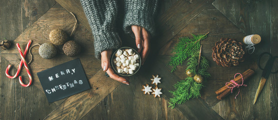 Christmas, New Year preparation background. Flat-lay of greeting card, glittering toy, woman's hands in grey sweater holding mug of hot chocolate, cinnamon, scissors over wooden table, top view