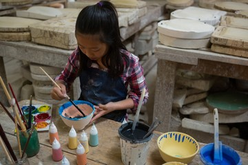 Attentive girl painting a bowl